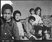 MIKAN 3586435 Five Inuit children seated outside [Left to right: unknown boy, Johnny (Kavavow?) Lyall, Pat Napatchee Lyall, Bella Ningyooga Wilcox (née Lyall) carrying baby Betty Novalinga Brewster (née Lyall), probably at Fort Ross, Nunavut]   [Summer 1948]. [Five Inuit children seated outside [Left to right: unknown boy, Johnny (Kavavow?) Lyall, Pat Napatchee Lyall, Bella Ningyooga Wilcox (née Lyall) carrying baby Betty Novalinga Brewster (née Lyall), probably at Fort Ross, Nunavut], [Summer 1948].]