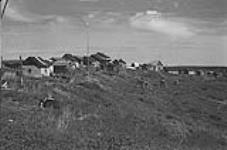 MIKAN 3327855 Indian cabins. Food caches are on posts. Fort Good Hope, N.W.T. ca. 1945 [Indian cabins. Food caches are on posts. Fort Good Hope, N.W.T., ca. 1945]