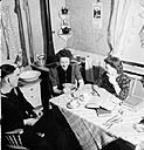 MIKAN 3203060 Female students of the University of Alberta entertaining a friend in the converted garage which is their boarding house. Mar. 1944 [Female students of the University of Alberta entertaining a friend in the converted garage which is their boarding house., Mar. 1944]