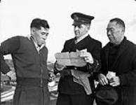 MIKAN 3193873 R.C.N. officer questioning Japanese-Canadian fishermen while confiscating their boat. 9 Dec. 1941 [R.C.N. officer questioning Japanese-Canadian fishermen while confiscating their boat., 9 Dec. 1941]