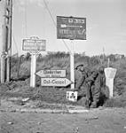 MIKAN 3251003 Lance-Corporal G.S. Archibald, 7th Field Company, Royal Canadian Engineers (R.C.E.), placing a sign next to German signs pointing to Dunkirk. Bergues, Belgium, 16 September 1944. September 16, 1944 [Lance-Corporal G.S. Archibald, 7th Field Company, Royal Canadian Engineers (R.C.E.), placing a sign next to German signs pointing to Dunkirk. Bergues, Belgium, 16 September 1944., September 16, 1944]