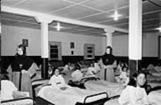 MIKAN 3598072 Turquetil Hall Residence (originally St. Mary's Residence), girls in their beds with two nuns, Chesterfield Inlet (Igluligaarjuk), Nunauvt, September 5, 1958    5 September 1958. [82 KB, 600 X 392]