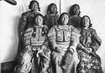 """MIKAN 3652534 [Photograph of six women with facial tattoos wearing parkas in front of a cloth backdrop. Niviaqsarjuk is seated in the centre in the first row] [Left to right back row: ?, Atunuck, Uckonuck, front row: Aka """"Pikey"""", Niviaqsajuk/Shoofly?, Taptaqut]    March 8, 1905. [[Photograph of six women with facial tattoos wearing parkas in front of a cloth backdrop. Niviaqsarjuk is seated in the centre in the first row] [Left to right back row: ?, Atunuck, Uckonuck, front row: Aka 'Pikey', Niviaqsajuk/Shoofly?, Taptaqut], March 8, 1905.]"""