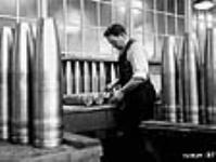 MIKAN 3195464 Male munitions worker measuring shells as part of testing process. Dec. 1939 [47 KB, 640 X 482]