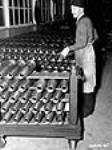 MIKAN 3195474 Workman in Canadian munitions factory piles up Bren gun shells for a coat of paint. Dec. 1939 [46 KB, 359 X 480]