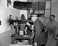 MIKAN 3195582 His Excellency the Earl of Athlone, Canada's Governor-General during World War II, fires a Bren gun into a special test room during inspection of a munitions plant. n.d. [65 KB, 640 X 501]