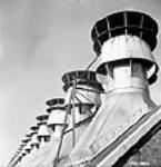 MIKAN 3196494 View of the ventilators of the rotary station outside the Arvida Aluminum Company of Canada plant. Jan. 1943 [39 KB, 466 X 480]
