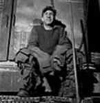MIKAN 3196520 Workman for the Arvida Aluminum Company of Canada plant poses, seated, dressed in clothing covered with layers of squares of cloth that act as insulation against the heat. Jan. 1943 [48 KB, 465 X 480]
