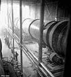 MIKAN 3196534 View of length of large long kiln used to dry out alumina oxide to alumina at the Arvida plant of the Aluminum Company of Canada. Jan. 1943 [44 KB, 449 X 480]