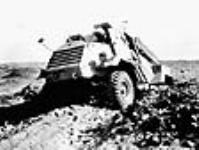 """MIKAN 3198185 Armoured renaissance car, """"The Otter"""", used in conflict in Tunisia, driving over rocky terrain. May 1943 [63 KB, 640 X 482]"""