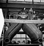 MIKAN 3197156 Workmen in the Canadian Vickers shipyard, Jean Rivet (emerging from the boiler) bucks rivets for Joe Hurd during construction of a Frigate in the Canadian Vickers yard. Sept. 1943 [67 KB, 463 X 480]