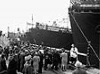 "MIKAN 3197217 Crowd gathers in front of a priest blessing the HMCS ""Cap de la Madeleine"" during her launch ceremony. May 1944 [54 KB, 640 X 474]"