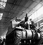 MIKAN 3197353 Workmen on the assembly line complete the final stages of installing a gun on a locomotive tank in the Montreal Locomotive Works plant. Summer 1943 [Workmen on the assembly line complete the final stages of installing a gun on a locomotive tank in the Montreal Locomotive Works plant., Summer 1943]