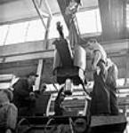 MIKAN 3197355 Workmen at the Montreal Locomotive Works plant use a crane to hoist a 25-pounder gun into place in a Montreal Locomotive tank. Summer 1943 [Workmen at the Montreal Locomotive Works plant use a crane to hoist a 25-pounder gun into place in a Montreal Locomotive tank., Summer 1943]