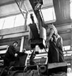 MIKAN 3197356 Workmen at the Montreal Locomotive Works plant use a crane to hoist a 25-pounder gun into place in a Montreal Locomotive tank. Summer 1943 [Workmen at the Montreal Locomotive Works plant use a crane to hoist a 25-pounder gun into place in a Montreal Locomotive tank., Summer 1943]