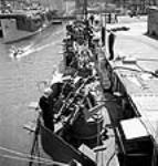 """MIKAN 3197402 Workmen test the sights on twin Oerlikon guns, newly installed on aircraft carrier escort vessels at Burrard Dry Dock to make sure bullets clear the bulwarks and give a fifteen-foot clearance over the flight deck."""". May 1944 [69 KB, 458 X 480]"""