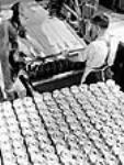 MIKAN 3627710 Des ouvriers surveillent une machine qui colle ensemble deux feuilles de papier d'amiante et qui les enroule sur un mandrin à l'usine Johns-Mainville Canada Inc. juin 1944 [61 KB, 362 X 480]