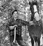 """MIKAN 3197737 Lumberman and """"skidder"""" Edoma Rozon of Mont Clerf, Quebec, poses with pulp hook on his shoulder with his horse, """"George"""". Mar. 1943 [55 KB, 458 X 480]"""
