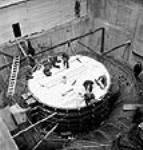 MIKAN 3197994 Overhead view of workmen working on the scrole case of the No. 9 unit inside the powerhouse during the Shipshaw Power Development project. Jan. 1943 [60 KB, 458 X 480]
