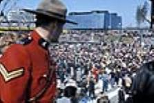 MIKAN 3198362 A Royal Canadian Mounted Police (RCMP) officer and crowd in front of the Quebec Pavilion at Expo 67. 1967 [A Royal Canadian Mounted Police (RCMP) officer and crowd in front of the Quebec Pavilion at Expo 67., 1967]