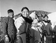 MIKAN 3603120 Another small group of Inuit in Cape Dorset [The late Timothy Ottochie is seen on the left, husband of Aukshuali (centre) who is holding her baby.]  1948. [Another small group of Inuit in Cape Dorset [The late Timothy Ottochie is seen on the left, husband of Aukshuali (centre) who is holding her baby.], 1948.]