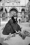 MIKAN 3198753 Nursing sister Marie-Antoinette Sirois of No. 6 Canadian General Hospital feeding pigeons in St. Mark's Square whileon leave in Venice, Italy  March 24-26, 1919. [Nursing sister Marie-Antoinette Sirois of No. 6 Canadian General Hospital feeding pigeons in St. Mark's Square whileon leave in Venice, Italy, March 24-26, 1919.]