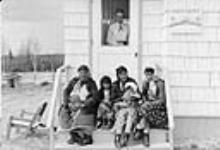 MIKAN 3603680 Mrs. Pulak, nurse at the Lansdowne nursing station, is watching from inside while [Indigenous] women and children sit on the front steps of the station  June 1957 [Mrs. Pulak, nurse at the Lansdowne nursing station, is watching from inside while [Indigenous] women and children sit on the front steps of the station, June 1957]