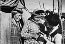 MIKAN 3603685 [Two women outside of their tent, while a field nurse is explaining the use of linement for sore muscles]  c 1955 [[Two women outside of their tent, while a field nurse is explaining the use of linement for sore muscles], c 1955]