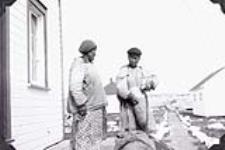 MIKAN 3613676 Two unidentified Inuit women outside Hudson's Bay trading post at Chesterfield Inlet. 1952 [65 KB]
