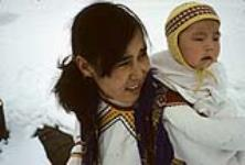 MIKAN 3613908 Young mother and her baby: the mother is wearing an amauti and her baby is wearing a yellow hat  [Damaris Ittukusuk Kadlutsiak was the first wife of Josiah Kadlutsiak of Igloolik. She is packing her son, Mike Kadlutsiak] [graphic material] May 1965. [77 KB, 760 X 512]