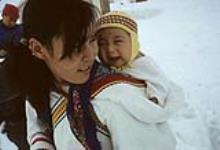 MIKAN 3613909 Young mother and her baby: the mother is wearing an amauti and her baby is wearing a yellow hat. [Damaris Ittukusuk Kadlutsiak  was the first wife of Josiah Kadlutsiak of Igloolik. She is packing her son, Mike Kadlutsiak]  [graphic material]    May 1965. [70 KB, 760 X 518]