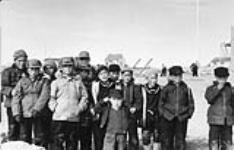 MIKAN 4698473 Externat fédéral Sir Joseph Bernier (Turquetil Hall), groupe de garçons debout sur le terrain de jeux de l¿école, Chesterfield Inlet (Igluligaarjuk), Nunavut, 5 septembre 1958 [Les étudiants comprennent: Joe Ataguttaaluk, Raymond Kaslak, Nicholas Pauktuut Arnatsiaq, Paul Manotick, Piita Irniq, Francois Nanorak, Yvo Junuk, et Timothy Qirnnguk]    5 septembre 1958. [60 KB, 600 X 384]