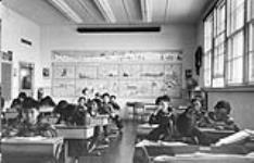 MIKAN 3614186 Sir Joseph Bernier Federal Day School (Turquetil Hall), group of students working at their desks in a classroom, Chesterfield Inlet (Igluligaarjuk), Nunavut, September 5, 1958. [1st row: Rene Otak is on far left; 2nd row: Pete Irniq is on the far right, beside him is Paul Manitok; 3rd row: Nick Anautinuq is on the far right; 4th row: Raymond Kalak is seated second from the left.] [graphic material] : September 5, 1958. [69 KB, 600 X 384]