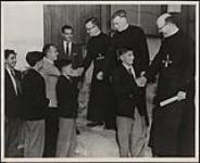 MIKAN 5188810 [A group of boys from Pessamit (formerly Bersimis) dressed in school uniform line up to shake the hands of priests]. [ca. 1958] [[A group of boys from Pessamit (formerly Bersimis) dressed in school uniform line up to shake the hands of priests]., [ca. 1958]]