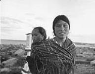 MIKAN 3855437 Inuit woman [Alice Sakitnaaq Tugak] carrying her baby [Rose Ooloooyukn] in Chesterfield Inlet (Igluligaarjuk), Nunavut  1948. [Inuit woman [Alice Sakitnaaq Tugak] carrying her baby [Rose Ooloooyukn] in Chesterfield Inlet (Igluligaarjuk), Nunavut, 1948.]