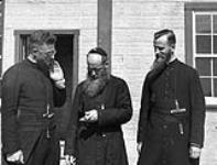 MIKAN 3855442 Three Roman Catholic Fathers, Father Fafard who was stationed at Repulse Bay (Naujaat) is in the middle, in Chesterfield Inlet (Igluligaarjuk), Nunavut  1948. [Three Roman Catholic Fathers, Father Fafard who was stationed at Repulse Bay (Naujaat) is in the middle, in Chesterfield Inlet (Igluligaarjuk), Nunavut, 1948.]