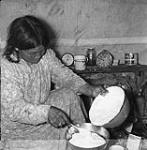 MIKAN 3855443 Elderly Inuit woman making bannock in Chesterfield Inlet (Igluligaarjuk), Nunavut  1948. [Elderly Inuit woman making bannock in Chesterfield Inlet (Igluligaarjuk), Nunavut, 1948.]