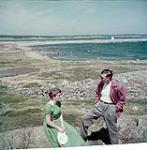 MIKAN 4292906 Man and woman on the beach in Fortress of Louisbourg National Historic Park, Nova Scotia. 1952 [191 KB, 1000 X 1019]