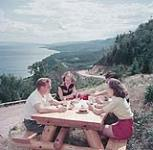 MIKAN 4292909 Two men and two women picnick on the Cabot Trail, Cape Breton Highlands National Park, Nova Scotia. 1952 [179 KB, 1000 X 977]