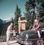 MIKAN 4317617 Un homme photographie une femme sur le capot d¿une voiture à côté d¿une enseigne indiquant la direction du lac Hector, en Alberta. juillet 1953 [256 KB, 1000 X 1017]