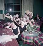 MIKAN 4293092 Nine female dancers in leotard wearing masks posing indoors for a photograph, Ste. Adele. August 1954 [177 KB, 1000 X 1049]