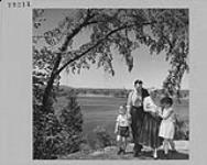 MIKAN 4297734 Recent immigrants to Canada Mr. & Mrs. T. Laing with Kenneth and Carolyn in park, Ottawa. March 1955 [Recent immigrants to Canada Mr. & Mrs. T. Laing with Kenneth and Carolyn in park, Ottawa., March 1955]