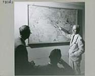 MIKAN 4297943 John English indicating departmental posts on the map to two Trade Commissioners in training. July 1955 [141 KB, 1000 X 799]