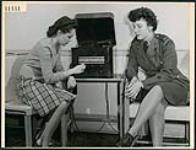 MIKAN 4317892 Mary Griffin et la soldate Rose Chimante, CWAC, écoutent les ¿uvres enregistrées de maîtres musiciens dans la salle de musique de la Bibliothèque publique de London en Ontario. mars 1945 [Mary Griffin et la soldate Rose Chimante, CWAC, écoutent les ¿uvres enregistrées de maîtres musiciens dans la salle de musique de la Bibliothèque publique de London en Ontario., mars 1945]