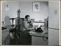 MIKAN 4318070 Gratien Gélinas, producteur et vedette des «Fridolinades», au téléphone dans son bureau. mars 1945 [129 KB, 1000 X 760]