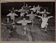 MIKAN 4310229 Onze jeunes femmes, membres du club «Knick-Knack» d'Ottawa, un club d'assistance canadien, pratiquant la gymnastique dans un YWCA d'Ottawa  mars 1946 [Onze jeunes femmes, membres du club «Knick-Knack» d'Ottawa, un club d'assistance canadien, pratiquant la gymnastique dans un YWCA d'Ottawa, mars 1946]