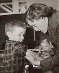 MIKAN 5196035 [Woman giving a young boy a needle]. 1953 [[Woman giving a young boy a needle]., 1953]