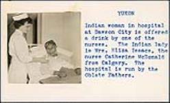 MIKAN 5196046 [Nurse Catherine McDonald gives Mrs. Eliza Isaac a drink]. 1953 [[Nurse Catherine McDonald gives Mrs. Eliza Isaac a drink]., 1953]