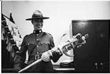 MIKAN 5196071 [Member of the RCMP holding the ceremonial mace of the Northwest Territories]. [between 1955-1963] [[Member of the RCMP holding the ceremonial mace of the Northwest Territories]., [between 1955-1963]]