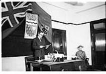 MIKAN 5196072 [Man delivering a speech behind a desk on which the ceremonial mace of the Northwest Territories is lying]. [between 1955-1963] [[Man delivering a speech behind a desk on which the ceremonial mace of the Northwest Territories is lying]., [between 1955-1963]]